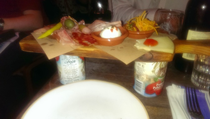 Cheese board sitting on cans of tomatoes