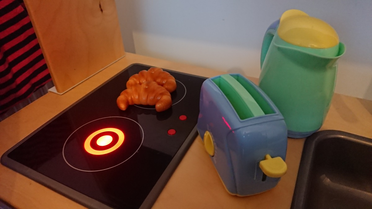 Toy croissants on a toy hob. The other hob is turned on.