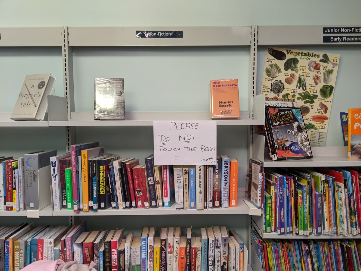 """A public library, with the sign """"Please do not touch the books, thank you"""""""