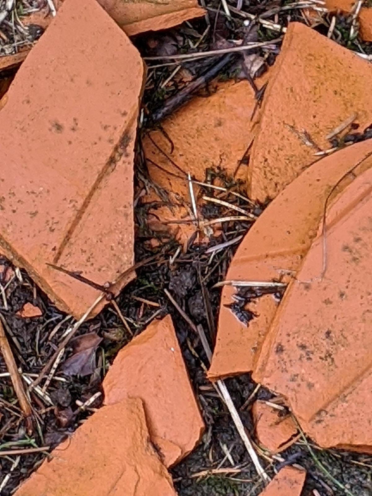 A broken plant pot in the dirt